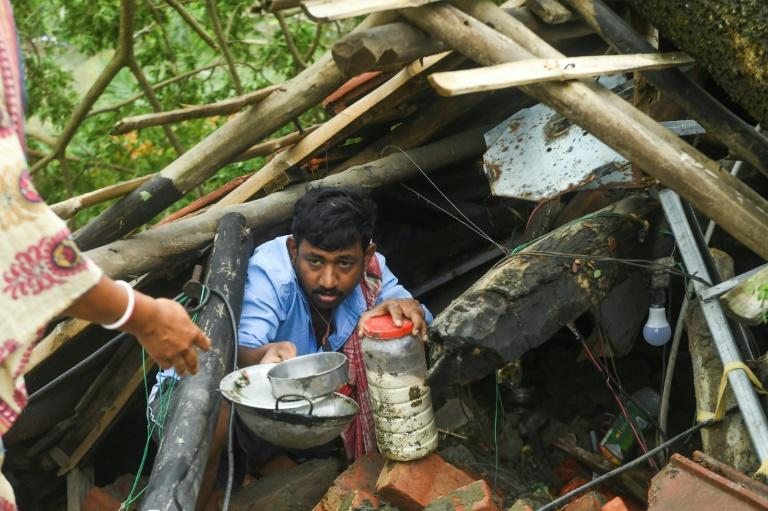 Villagers salvage items from their houses damaged by Cyclone Amphan in the Indian state of West Bengal