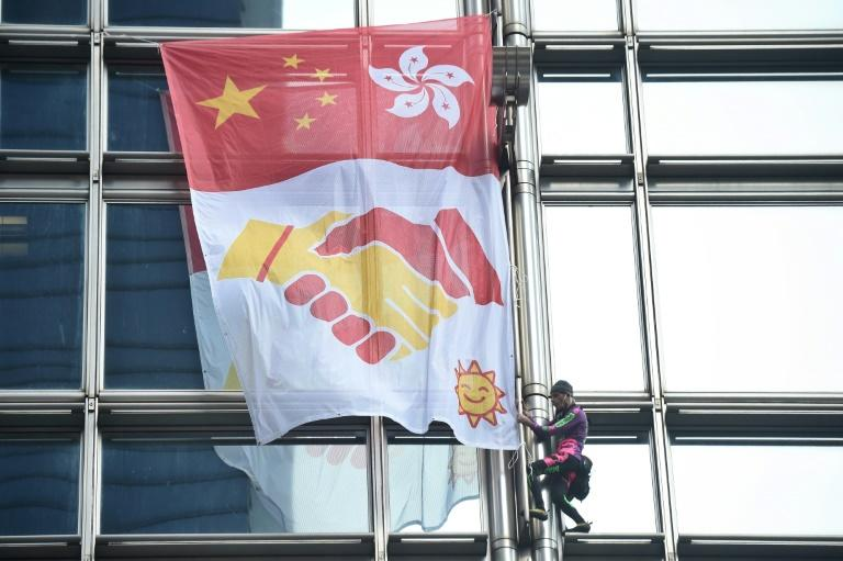 "Alain Robert, popularly known as the ""French Spiderman"", scaled a Hong Kong skyscraper and unfurled a banner"