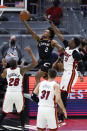 Cleveland Cavaliers' Collin Sexton (2) shoots against Miami Heat's Bam Adebayo (13), Max Strus (31) and Andre Iguodala (28) during the second half of an NBA basketball game, Saturday, May 1, 2021, in Cleveland. (AP Photo/Ron Schwane)