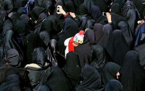 An Iranian woman carry her child as she attends the funeral of 27 Revolutionary Guards, who were killed in a suicide attack, in the southeastern city of Isfahan - Credit: AFP