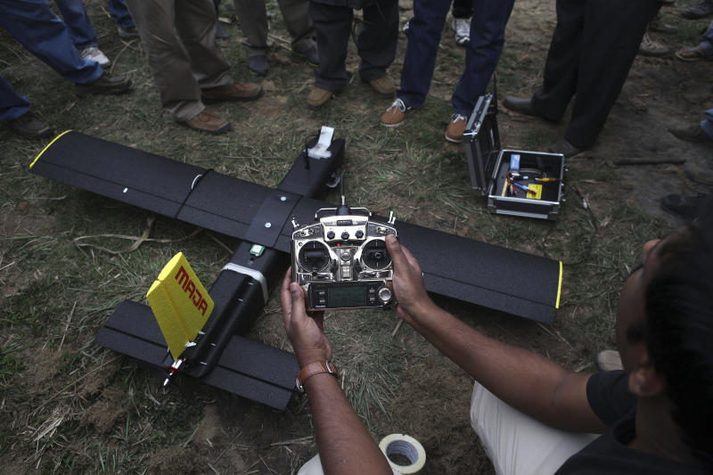 An official tests an unmanned aircraft or drone before its first flight at the Kaziranga National Park at Kaziranga in Assam state, India, Monday, April 8, 2013. Wildlife authorities used drones on Monday for aerial surveillance of the sprawling natural game park in northeastern India to protect the one-horned rhinoceros from armed poachers. The drones will be flown at regular intervals to prevent rampant poaching in the park located in the remote Indian state of Assam. The drones are equipped with cameras and will be monitored by security guards, who find it difficult to guard the whole 480-square kilometer (185-square mile) reserve. (AP Photo/Anupam Nath)