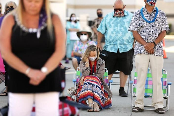 """Worshippers gather in the parking lot for a church service at Calvary Chapel of Temecula on July 26. <span class=""""copyright"""">(Los Angeles Times)</span>"""