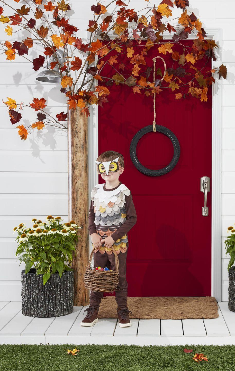 <p>Create a friendly owl house with this fun DIY tree and tire swing wreath.</p><p><strong>Make the tree</strong><strong>:</strong> Wrap a tall mailing tube in wood grain contact paper. Attach it to the door frame with nails or double sided velcro. Stuff fall branches into the top of the tube, holding them in place with nails. </p>