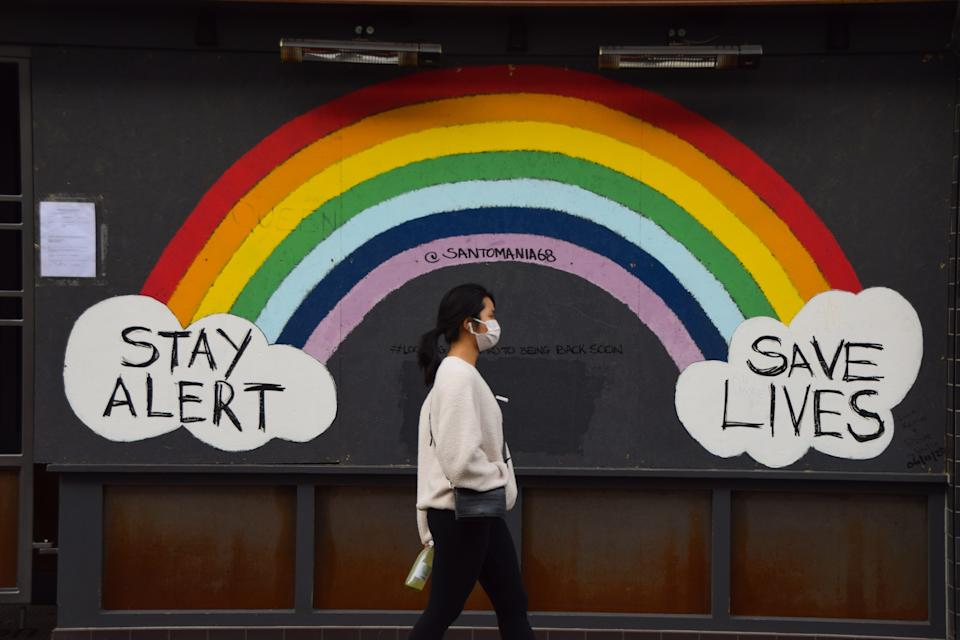 A woman wearing a face mask as a precaution walks past a Stay Alert, Save Lives rainbow sign in Soho. England is set to enforce a tough tier system once the lockdown ends on 2 December. (Photo by Vuk Valcic / SOPA Images/Sipa USA)