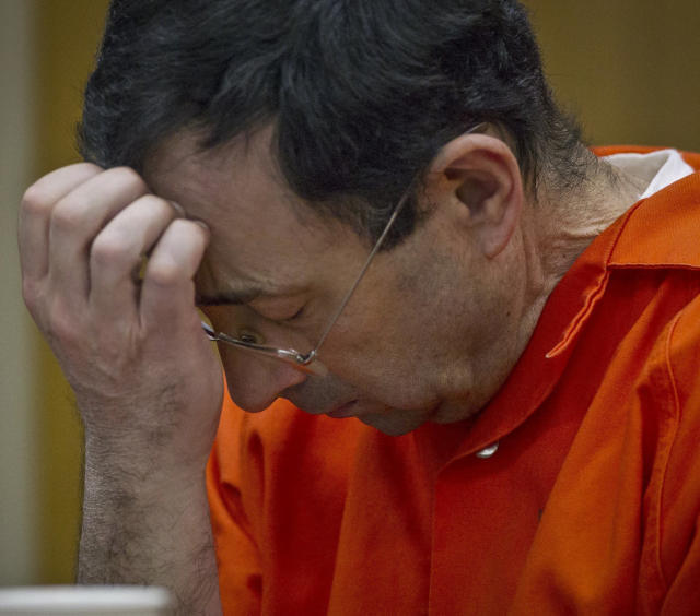 FILE - This Jan. 31, 2018 photo shows former Michigan State University sports-medicine and USA Gymnastics doctor Larry Nassar during his criminal sexual abuse sentencing at Eaton County Circuit Court in Charlotte, Mich. Michigan's 15 public universities on Monday, March 12, 2018, asked the Legislature to delay voting on bills inspired by the Larry Nassar sexual abuse case, expressing concern about measures that would retroactively extend the time victims would have to file lawsuits and remove an immunity defense for governmental agencies. (Cory Morse/The Grand Rapids Press via AP, File)