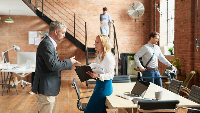 Busy trendy office with business people achieving success.