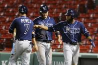 Tampa Bay Rays' Yoshitomo Tsutsugo, center, and Manuel Margot, right, walk to the dug out past Michael Perez (7) after scoring on a two-run double by Kevin Kiermaier during the seventh inning of a baseball game against the Boston Red Sox, Monday, Aug. 10, 2020, in Boston. (AP Photo/Michael Dwyer)