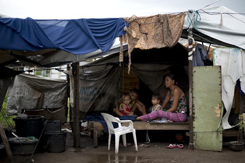 A mother takes care of her children on October 14, 2014 at a tent city in Tacloban, which was devastated by Super Typhoon Haiyan in 2013
