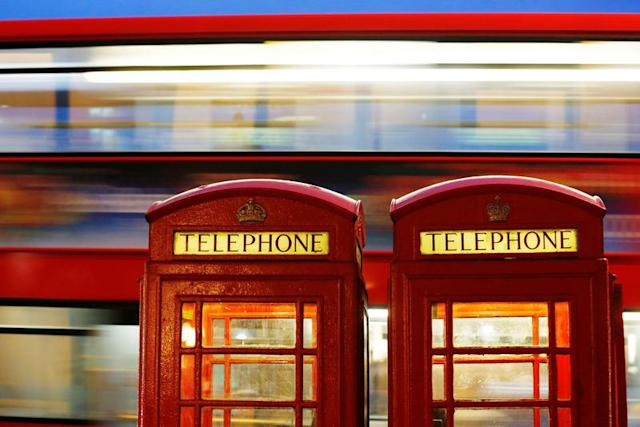 A bus passes traditional telephone boxes in London, Britain, November 3, 2013. REUTERS/Luke MacGregor/File Photo