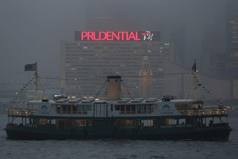 A ferry sails past an advertisement of Prudential Assurance under foggy weather at the Victoria Harbour in Hong Kong