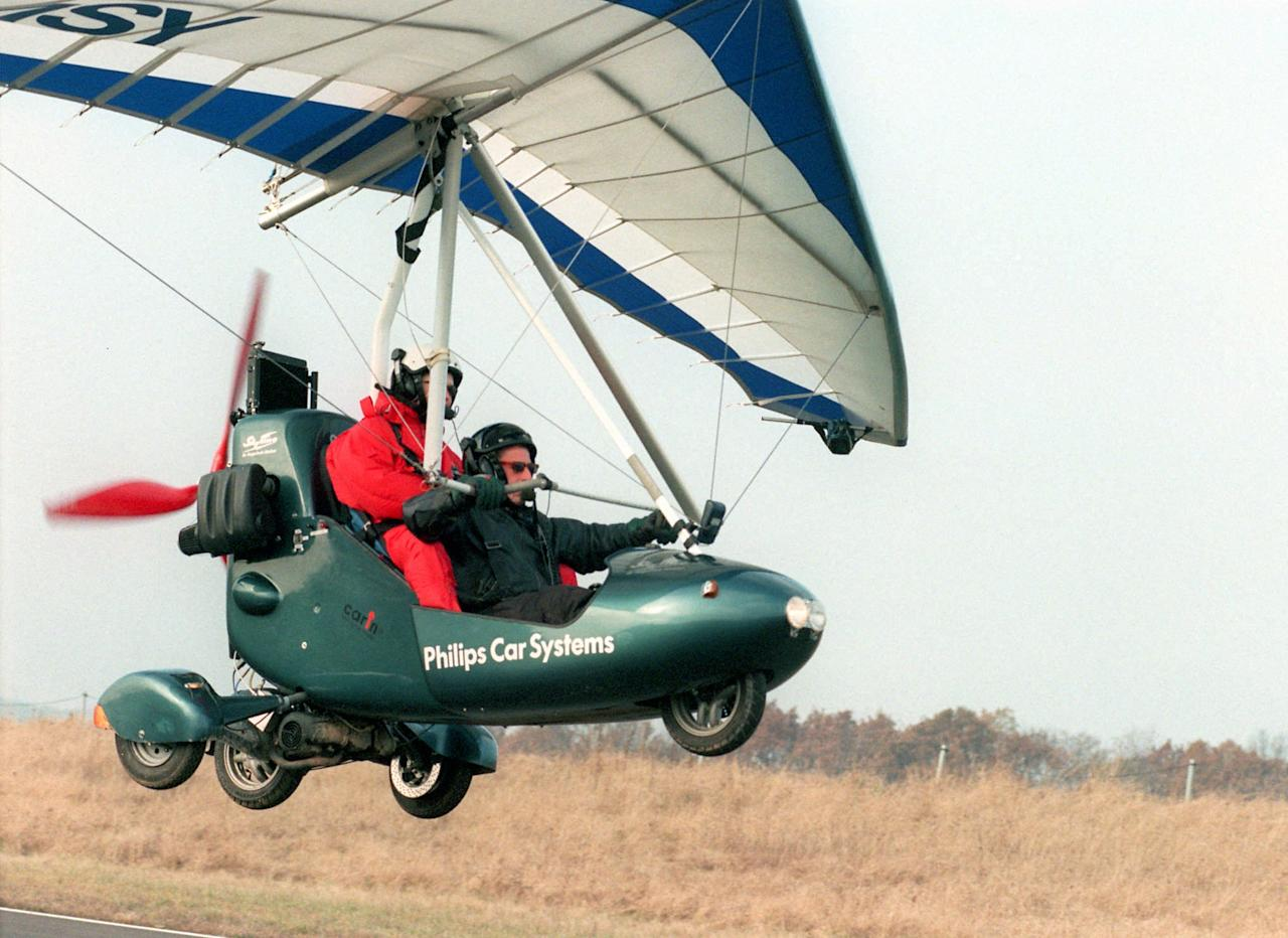 Pilot instructor Mathias Klug, front right, and student Mirja Gutzer, red overall,  are about to make a landing with their Skyline Event GTS, near Giessen, north of Frankfurt, Germany, on this photo taken Monday, Nov.17, 1997. It took Klug 2 1/2 years to develop and build the peculiar hybrid car-plane that can fly at a speed of 120km/h (72 mls/h) and can go at least 50 km/h (30mls/h) on the ground after removing the wings. The Skyline Event GTS can be ordered at 90,000 marks (dlrs 52,000). Klug said the idea behind was to find a solution that permitted air travelling and further mobility after arriving at the landing ground, like driving to the next beer garden. (AP Photo/Axel Seidemann)