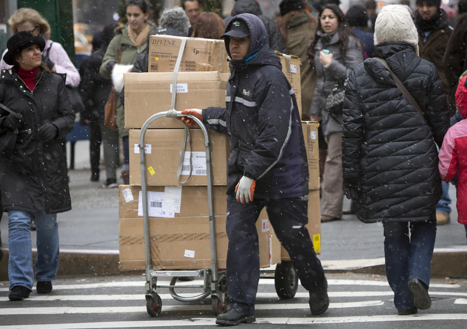 A FedEx delivery person wheels a cart full of packages down 5th Avenue in New York. Some people may want to ship packages instead of checking them on flights. (REUTERS/Carlo Allegri)