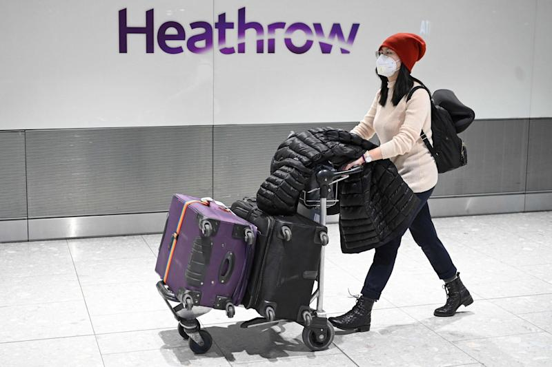 Passengers wear face masks as the push their luggage after arriving from a flight at Terminal 5 of London Heathrow Airport (AFP via Getty Images)