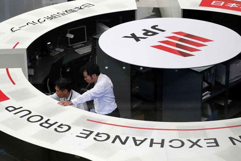 FILE PHOTO: Employees of the Tokyo Stock Exchange (TSE) work at the bourse in Tokyo, Japan, October 11, 2018. REUTERS/Issei Kato/File Photo