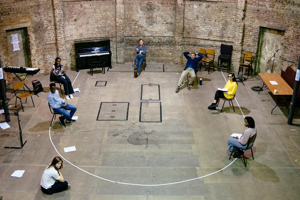 <p>The cast of Nine Lessons and Carols rehearse on the Almeida stage</p> (Helen Murray)