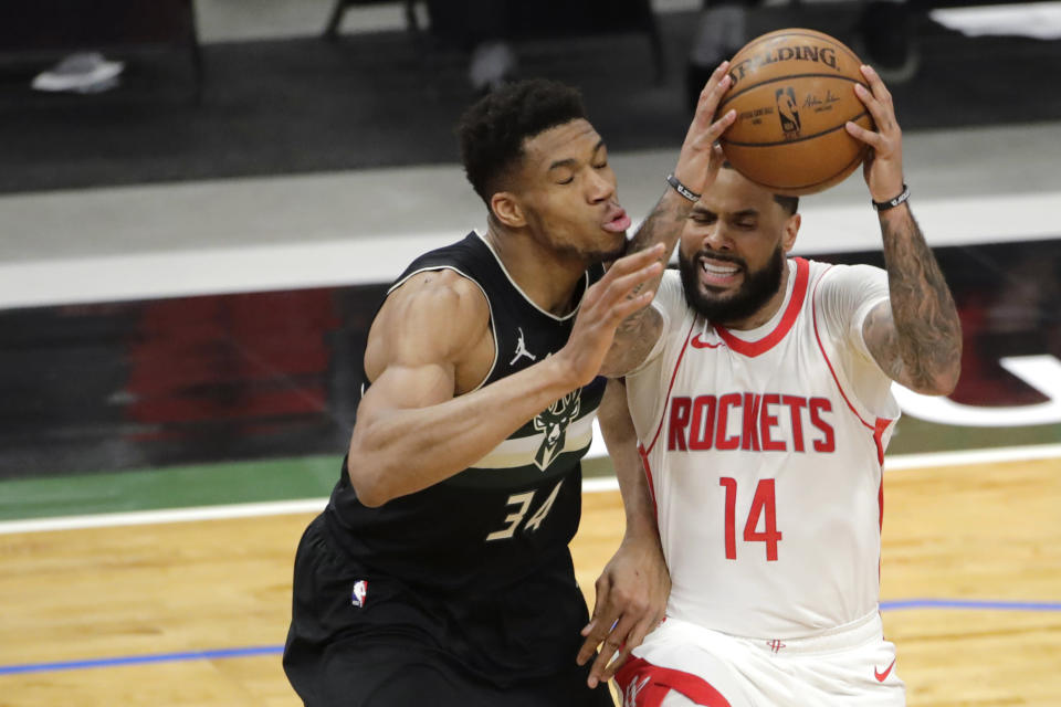Houston Rockets' D.J. Augustin (14) drives to the basket against Milwaukee Bucks' Giannis Antetokounmpo (34) during the first half of an NBA basketball game Friday, May 7, 2021, in Milwaukee. (AP Photo/Aaron Gash)