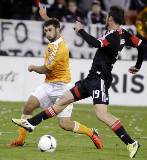 Houston Dynamo's Will Bruin, left, kicks the ball as D.C. United's Emiliano Dudar (19) defends during the second half of the second game of an MLS soccer Eastern Conference final playoff series, Sunday, Nov. 18, 2012, in Washington. The Dynamo advanced to their second straight MLS Cup final and fourth in seven years, tying D.C. United 1-1 Sunday for a 4-2 aggregate win in the Eastern Conference final. (AP Photo/Luis M. Alvarez)