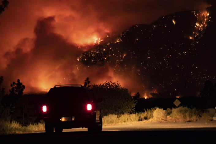 A motorist watches from a pullout on the Trans-Canada Highway as a wildfire burns on the side of a mountain in Lytton, B.C., Thursday, July 1, 2021. (Darryl Dyck/The Canadian Press via AP)