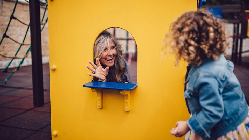 Happy retired grandmother and little granddaughter having fun playing make believe game together at playground.