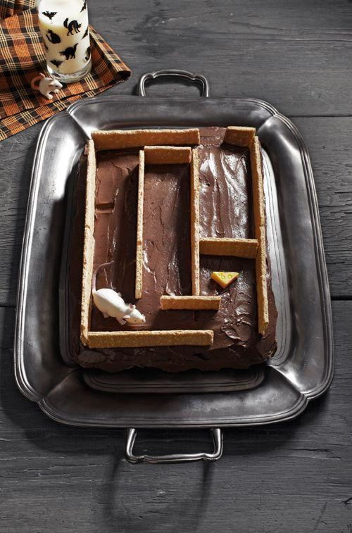 """<p>This little labyrinth takes the cake when it comes to speedy assembly time.</p><p>To begin, you'll need graham crackers (we used five sheets of four crackers), a rubber mouse, and a lemon Starburst candy.</p><p>Using the photo as a guide, arrange the crackers atop the cake to form the maze walls, breaking the crackers into smaller pieces as necessary. (To make clean breaks, first use a sharp knife to score the fronts and backs of the crackers.)</p><p>Create the cheese by cutting the Starburst diagonally in half, then using a clean cocktail straw to make indentations atop the candy. Place the candy in one spot of the maze and the mouse in another. </p><p><strong><a href=""""https://www.countryliving.com/food-drinks/recipes/a37728/rich-chocolate-frosting-recipe/"""" rel=""""nofollow noopener"""" target=""""_blank"""" data-ylk=""""slk:Get recipe for chocolate frosting"""" class=""""link rapid-noclick-resp"""">Get recipe for chocolate frosting</a>.</strong></p>"""