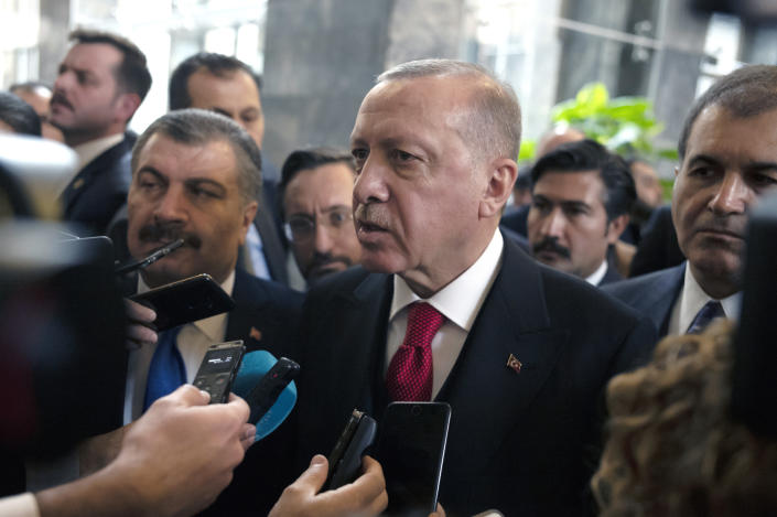 Turkish President Recep Tayyip Erdogan speaks to journalists at the parliament, in Ankara, Turkey, Wednesday, Feb. 12, 2020. Erdogan said Wednesday that Turkey will attack government forces anywhere in Syria if another Turkish soldier is injured.(AP Photo/Burhan Ozbilici)