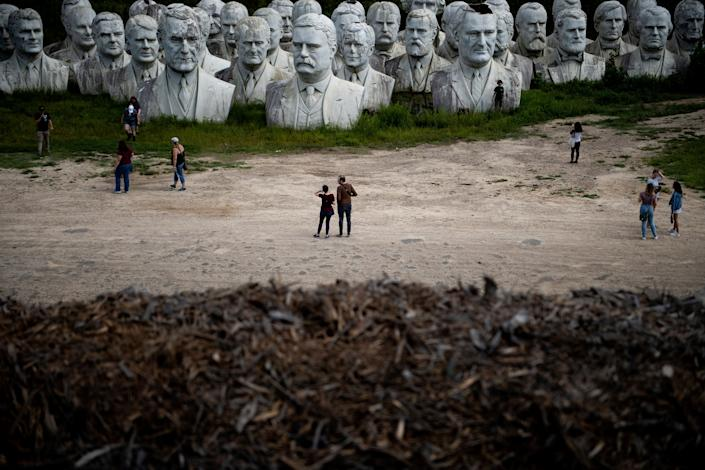 People tour the decaying remains of salvaged busts of former US Presidents August 25, 2019, in Williamsburg, Virginia. (Photo: Brendan Smialowski/AFP/Getty Images)