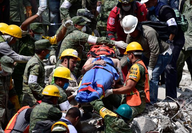 <p>A survivor is pulled out of the rubble from a flattened building in Mexico City on Sept. 20, 2017 as the search for survivors continues a day after a strong quake hit central Mexico. (Photo: Pedro Pardo/AFP/Getty Images) </p>