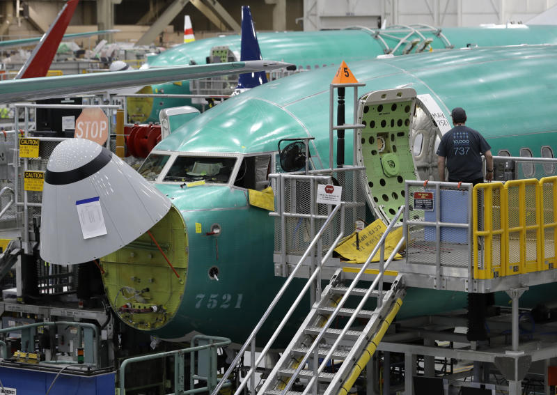 FILE - In this March 27, 2019, file photo, a worker enters a Boeing 737 MAX 8 airplane during a brief media tour of Boeing's 737 assembly facility in Renton, Wash. On Monday, Dec. 16, shares of Boeing are falling before the opening bell on a report that the company may cut production of its troubled 737 Max or even end production all together. (AP Photo/Ted S. Warren, File)