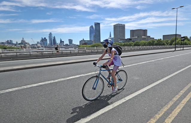 A woman wears a mask while riding a bike in London. (Getty Images)