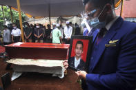 A colleague holds a portrait of Okky Bisma, a flight steward, one of victims of the crashed Sriwijaya Air passenger jet during his funeral in Jakarta, Indonesia.Thursday, Jan. 14, 2021. An aerial search for victims and wreckage of the crashed Indonesian plane expanded Thursday as divers continued combing the debris-littered seabed looking for the cockpit voice recorder from the lost Sriwijaya Air jet. (AP Photo)