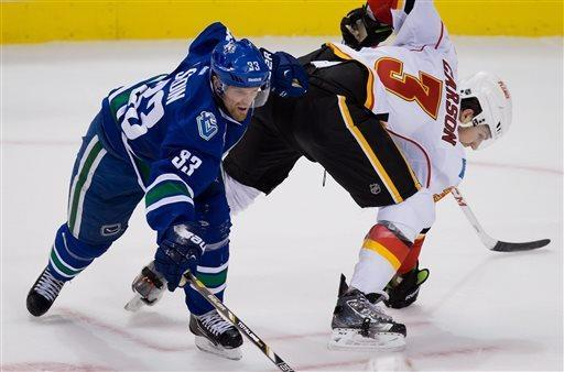 Vancouver Canucks' Henrik Sedin, left, of Sweden, collides with Calgary Flames' Brett Carson during the second period of an NHL hockey game in Vancouver, British Columbia, on Saturday April 6, 2013. (AP Photo/The Canadian Press, Darryl Dyck)