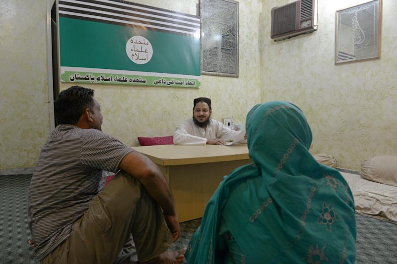 Mufti Muhammad Zia Madni (C), member of provincial peace committee, listens to married couple Sajjad (L) and Qamar (R), elder sister of young woman Zunera in Pakistand on May 8, 2014 (AFP Photo/Farooq Naeem)