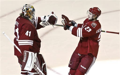 Phoenix Coyotes' Mike Smith (41) celebrates his shutout against the Dallas Stars with teammate Oliver Ekman-Larsson (23), of Sweden, at the end of an NHL hockey game Saturday, Feb. 2, 2013, in Glendale, Ariz. The Coyotes defeated the Stars 2-0.(AP Photo/Ross D. Franklin)