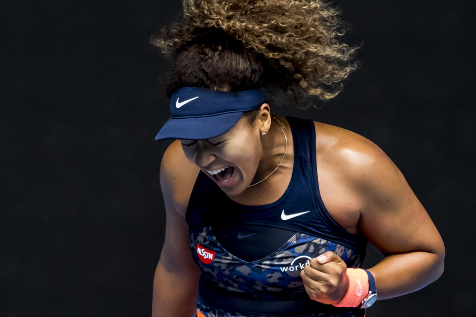 Naomi Osaka pumps her fist and yells to celebrate.