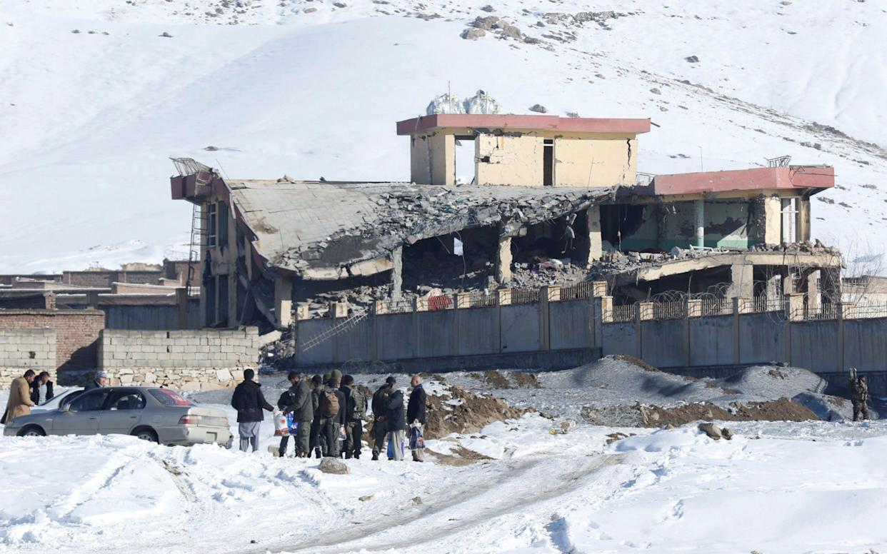 Men stand in front of a collapsed building of a military base after a car bomb attack in Maidan Wardak - REUTERS