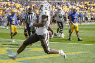 Western Michigan running back Sean Tyler (9) dashes through the end zone after scoring a touchdown against the Pittsburgh defense during the first half of an NCAA college football game, Saturday, Sept. 18, 2021, in Pittsburgh. (AP Photo/Keith Srakocic)