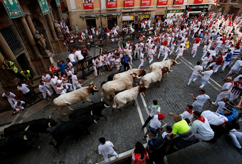 Revellers sprint near bulls and steers during the running of the bulls at the San Fermin festival in Pamplona, Spain, July 11, 2019. (Photo: Susana Vera/Reuters)