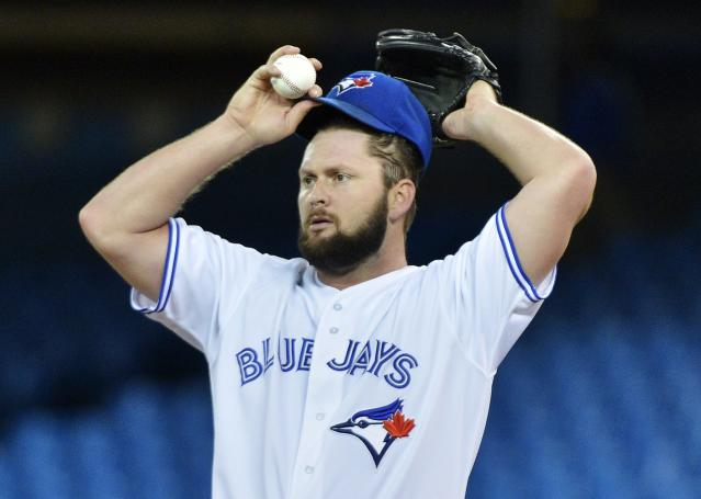 Toronto Blue Jays starting pitcher Todd Redmond pauses as he works against the Baltimore Orioles during the first inning of a baseball game in Toronto on Friday, Sept. 13, 2013. (AP Photo/The Canadian Press, Nathan Denette)