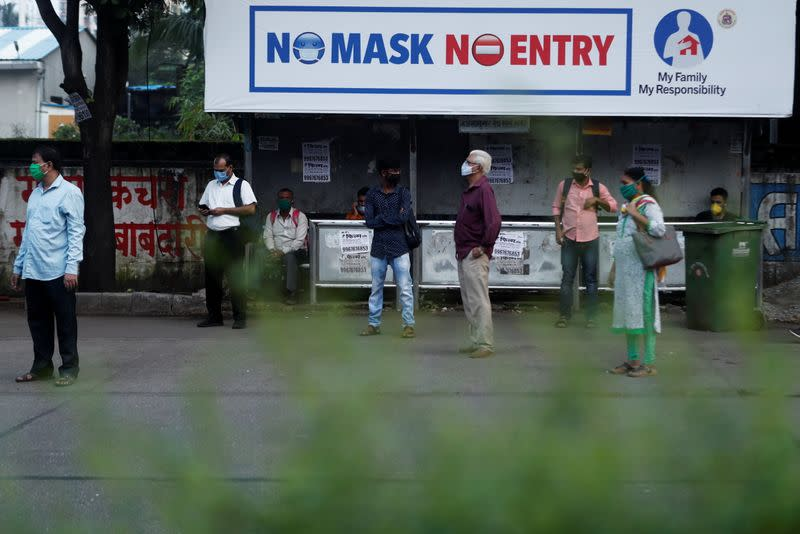 People wearing protective masks wait at a bus stop amidst the spread of the coronavirus disease (COVID-19), in Mumbai