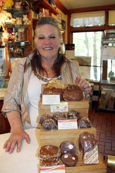 This July 30, 2012 photograph provided by the Estes Park News shows Jo Adams the owner of the Rocky Mountain Chocolate Factory in her store in Estes Park, Colo. A black bear went in and out of the candy store multiple times on July 25, 2012. He used the front door and didn't break a thing. He did, however, steal some treats. (AP Photo/Estes Park News, Kris Hazelton)