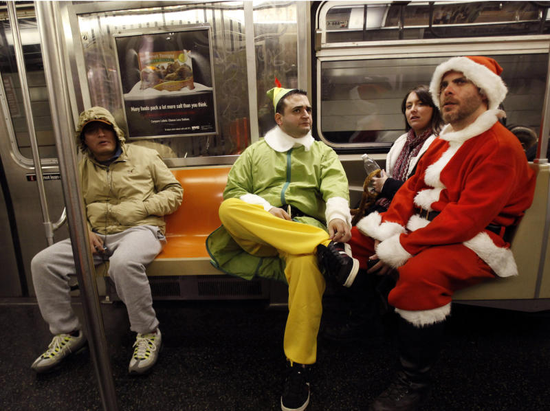 FILE - In this Dec. 11, 2010 file photo, John Paul, center, of Manhattan, dressed as an Elf and Michael Smallwood, of Brooklyn, dressed as Santa ride the E train downtown in New York for the annual SantaCon pub crawl where participants dress up in Santa and other Christmas themed outfits. SantaCon may be coming to town again, but not everyone is happy about it. Revelers will gather on Saturday, Dec. 14, 2013 for the holiday tradition of bar-hopping that has drawn the ire of New Yorkers, who complain of misbehavior, and the NYPD, which is asking bars not to serve the Santa. (AP Photo/Mary Altaffer, File)