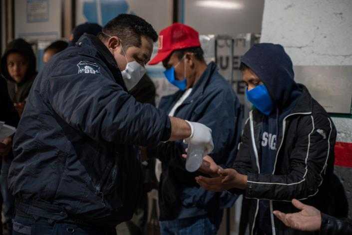 """Chihuahua State Police gives out hand sanitizer to migrants on April 6, 2020 at the Paso del Norte International Bridge in Ciudad Jua?rez in the state of Chihuahua, Mexico. - As immigration courts have been closed due to the coronavirus, COVID-19, pandemic people seeking asylum in Migrant Protection Protocols program, better known as the """"Remain in Mexico"""" policy, are still expected to show up in the dangerous city centre before dawn to receive new dates despite stay-at-home order on both sides of the border. (Photo by Paul Ratje / Agence France-Presse / AFP) (Photo by PAUL RATJE/Agence France-Presse/AFP via Getty Images)"""