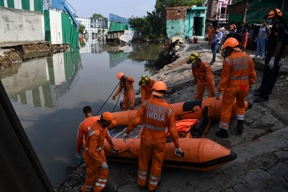 National Disaster Response Force personnel prepare to inspect on a dinghy the area where some shanty houses collapsed into a canal due to heavy rains in New Delhi on July 19, 2020. (Photo by Sajjad HUSSAIN / AFP) (Photo by SAJJAD HUSSAIN/AFP via Getty Images)