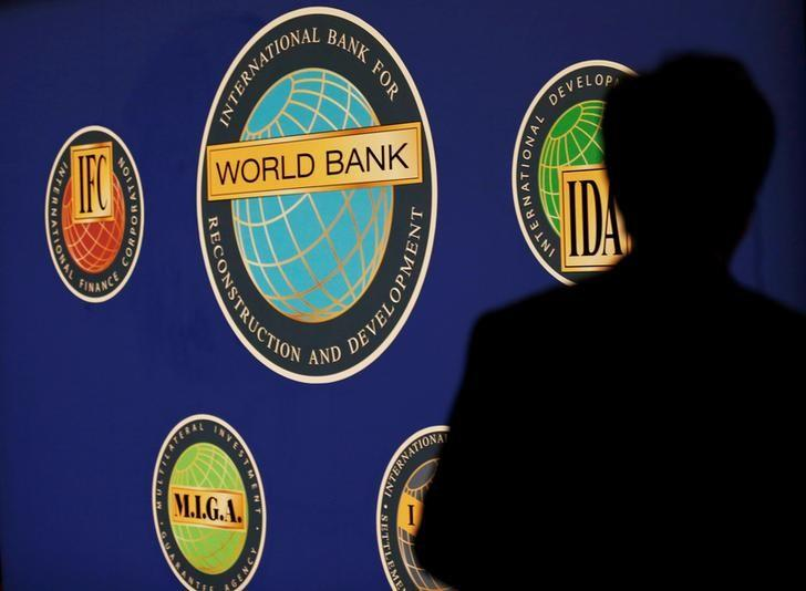 FILE PHOTO: Man is silhouetted against logo of World Bank at main venue for IMF and World Bank annual meeting in Tokyo