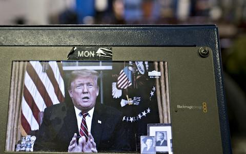 A television monitor in the White House press briefing room broadcasts U.S. President Donald Trump's address on border security in Washington, D.C. on Tuesday - Credit: Andrew Harrer/Bloomberg