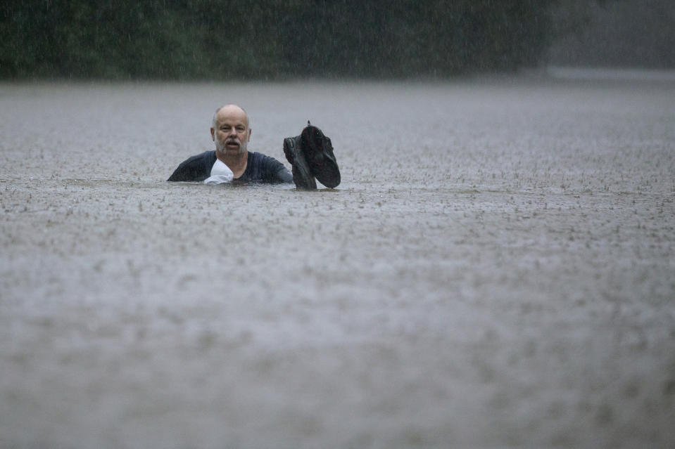 A man wades out through floodwaters caused by heavy rain spawned by Tropical Depression Imelda inundated the area on Sept. 19, 2019, in Patton Village, Texas. (Photo: Brett Coomer/Houston Chronicle via AP)