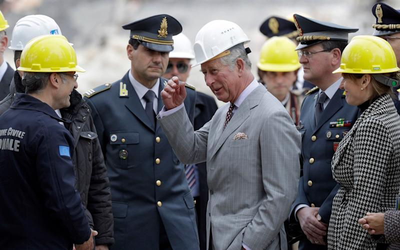 Britain's Prince Charles, center, wears a helmet as he speaks with Fabrizio Curcio, head of the Italian Civil Protection, left, during his visit to the 2016 earthquake-hit town of Amatrice - Credit: Andrew Medichini/AP