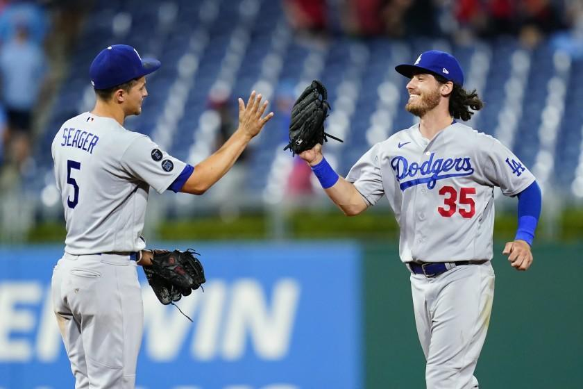 Los Angeles Dodgers' Corey Seager, left, and Cody Bellinger celebrate after the Dodgers won a baseball game against the Philadelphia Phillies, early Wednesday morning, Aug. 11, 2021, in Philadelphia. (AP Photo/Matt Slocum)
