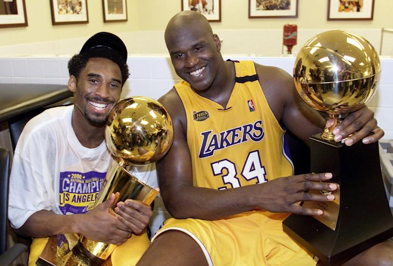 Lakers' Kobe Bryant holds the Larry O'Brien trophy as teammate Shaquille O'Neal holds the MVP trophy.
