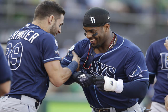 Tampa Bay Rays' Yandy Diaz, right, is congratulated by Kevin Kiermaier after hitting a solo home run against the Oakland Athletics during the first inning of an American League wild-card baseball game in Oakland, Calif., Wednesday, Oct. 2, 2019. (AP Photo/Ben Margot)